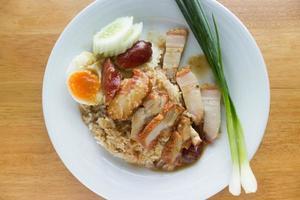 grillat fläsk och skivat kokt ägg med ris och grönsaker på den vita plattan på bordet