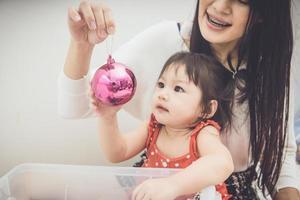 lycklig familjemor och bebis som leker hem på julhelgen