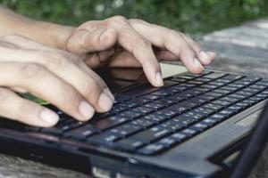 handperson som arbetar och använder på en bärbar dator för frilans med ingångstangentbord för online-bloggerjobb till svart dator på ett träbord hemma. foto