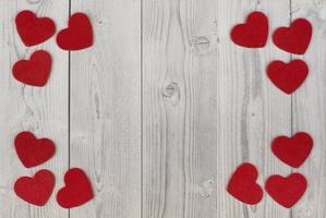 röda hjärtan i hörnen på en vit och grå träbakgrund. begreppet alla hjärtans dag foto