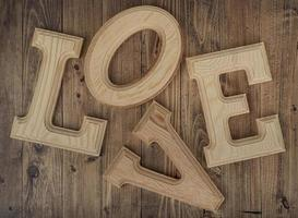 stökiga träbokstäver som bildar ordet kärlek på en valnötträbakgrund. begreppet st. alla hjärtans dag