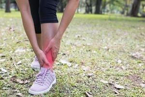 kvinna som håller sin fotled i smärta foto