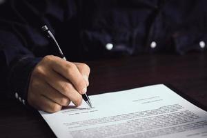 person som undertecknar ett kontrakt foto