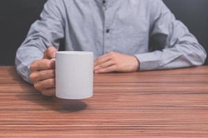 man som håller en kaffekopp vid sitt skrivbord foto