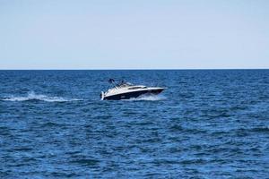 vit motorbåt på havet under dagtid