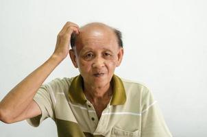 gammal asiatisk man som kliar huvudet foto