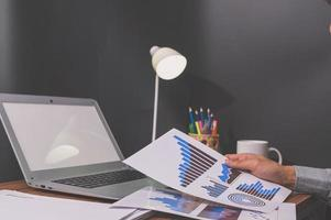 affärsmän sitter på jobbet och kollar dokument vid skrivbordet i rummet foto