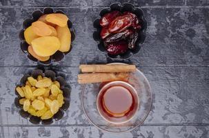 ovanifrån av torkade frukter russin aprikoser och torkade datum i minitårta burkar serveras med te på svart trä bakgrund