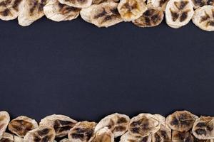 ovanifrån av torkade bananchips isolerad på svart bakgrund med kopieringsutrymme foto