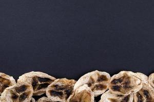 ovanifrån av torkade bananchips ordnade längst ner på svart bakgrund med kopieringsutrymme foto