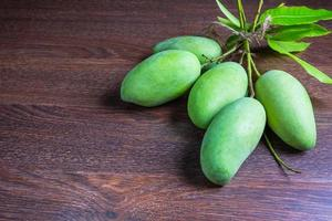 färsk grön mangofrukt på ett träbord foto