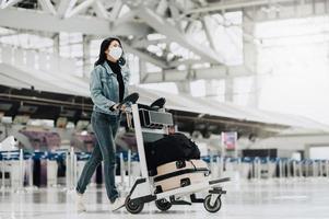 kvinna som bär mask som går med bagage