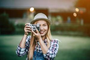 ung kvinna poserar med retro filmkamera foto