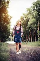 ung glad flicka som går i en skog på sommaren