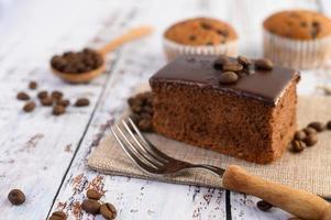 chokladkaka på säcken och kaffebönor med gaffel på ett träbord.