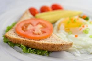 ett stekt ägg med rostat bröd, morötter, majs och vårlök foto