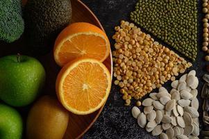 baljväxter med apelsiner, kiwi och äpple på en svart bakgrund