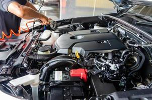 mekaniker som rengör bilmotorn foto