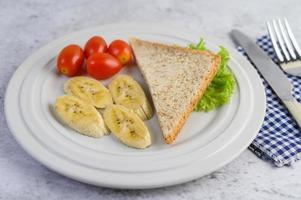 bröd med banan och tomater på en vit platta foto