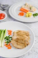 ångad kycklingbröst på en vit tallrik med vårlök och morötter