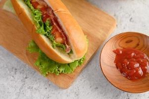 hotdog med sallad och tomat på en träskärbräda