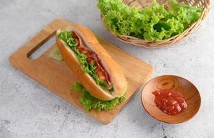 hotdog med sallad och tomat på en träskärbräda foto