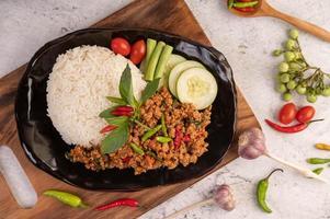 kryddig malet fläsksallad med ris, chili och tomater på en svart tallrik