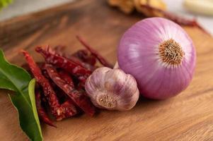 rödlök, peppar och lime blad på ett träbord foto