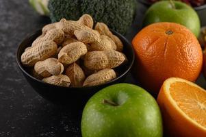 närbild av jordnötter, apelsiner och äpplen foto