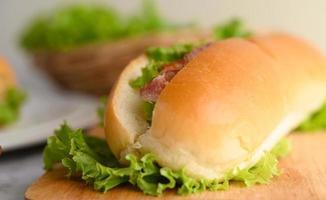 närbild av en hotdog med bacon på träskärbräda foto