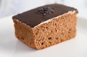 chokladkaka på en vit platta och ett vitt träbord