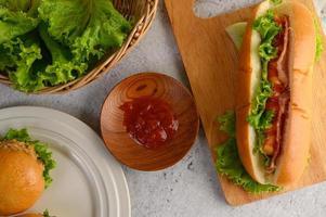 hamburgare och korv med salladsbacon och tomatsås foto