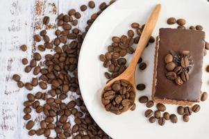 chokladkaka på en vit platta och kaffebönor