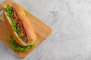 stor hotdog med sallad på träskärbräda