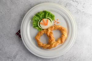 kringla på en vit skål med sallad och morötter