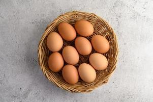färska bruna ägg i en flätad korg