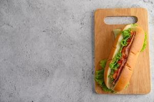 stor hotdog med sallad på träskärbräda foto