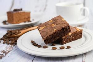 choklad brownies på en vit platta och kaffebönor på en träsked foto