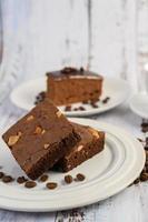 chokladkaka på en vit platta och kaffebönor foto
