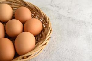 färska bruna ägg i en flätad korg foto