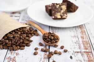kaffebönor i en träsked och hampasäckar på ett vitt träbord