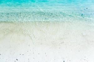 vit sand med blått vatten