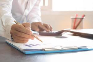 affärsperson som skriver med en guldpenna foto