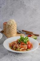 thailändsk papayasallad på en vit tallrik med klibbigt ris, chili, sked och gaffel foto