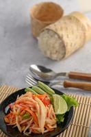 thailändsk papayasallad på en svart tallrik med klibbigt ris foto