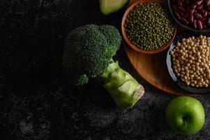broccoli, äpple och bönor på en svart cementgolvbakgrund