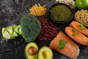 baljväxter, broccoli, frukt och lax på svart cementbakgrund foto