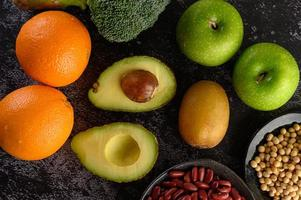 broccoli, äpple, apelsin, kiwi, avokado och bönor på en svart cementgolvbakgrund foto