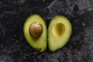 halverad avokado på svart cement foto