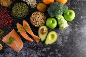 baljväxter, broccoli, frukt och lax på svart cementbakgrund